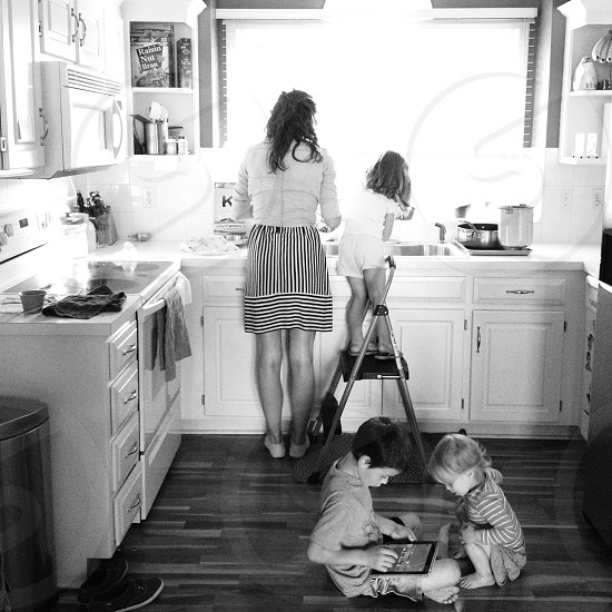 woman in a kitchen with her children photo photo