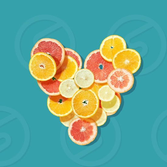 Fresh fruits heart on blue background. Valentine postcard photo