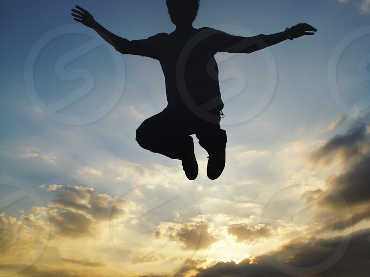 boy jumping with his knees up photo