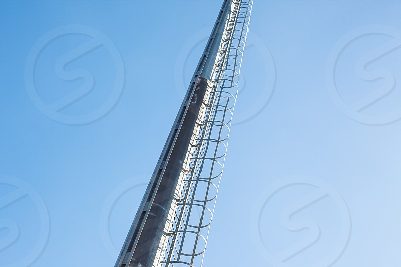 Conceptual composition of high metal ladders and blue sky.  photo
