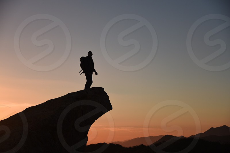 man standing on tall rock at sunset photo