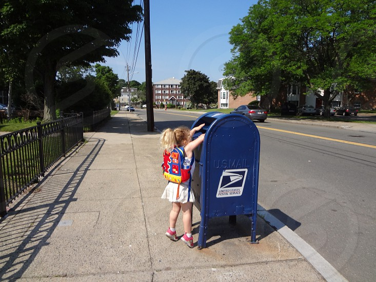 Child preschooler mailing letter to pen pal reaching mailbox urban city street photo