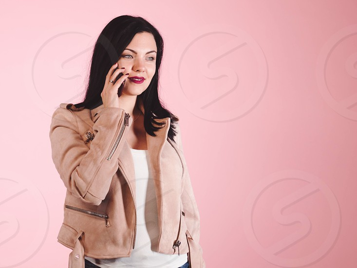 Smiling young woman in leather jacket talking on the phone isolated on pink background. Trendy girl using technology. Smartphone and conversation concept. photo