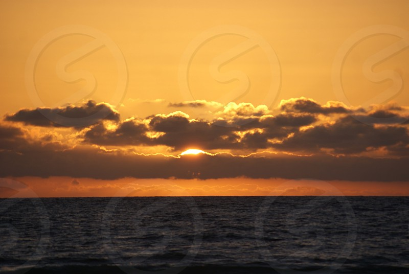 Sun setting in the ocean behind the clouds photo