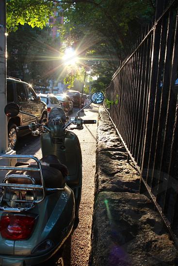 green motor scooter near black steel fence photo