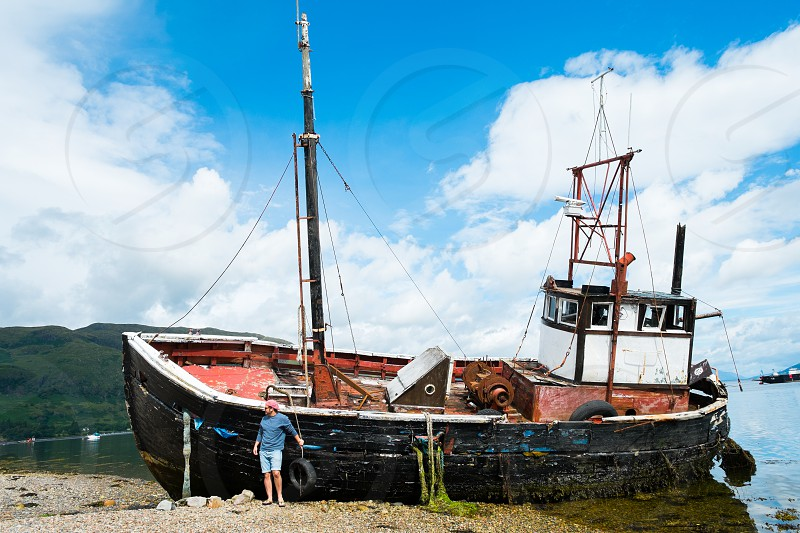 Old Fishing boat in Scotland with a young man standing next to it wearing a cap and sun glasses photo