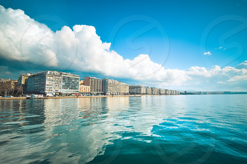 brown concrete buildings near blue body of  water under white and blue cloudy sky during daytime photo