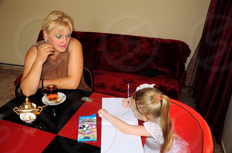 woman shoulders leaning on table beside girl doing drawing photo