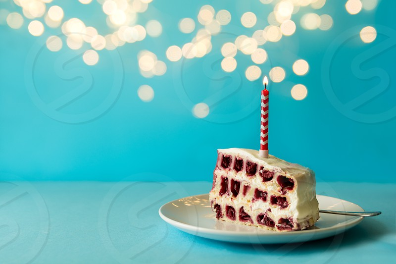 Slice of white birthday cherry cake with colorful candles on blue background against defocused light. Holiday celebration concept. Copy space photo