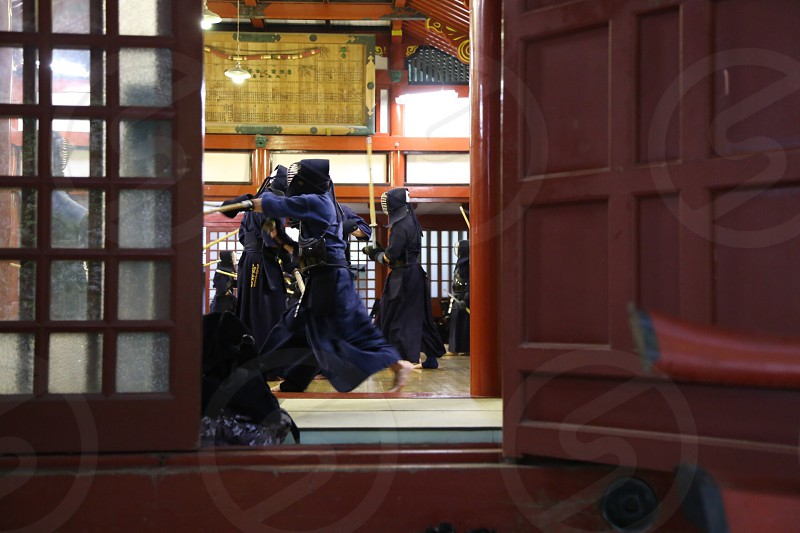 person wearing kendo while fighting inside dojo photo