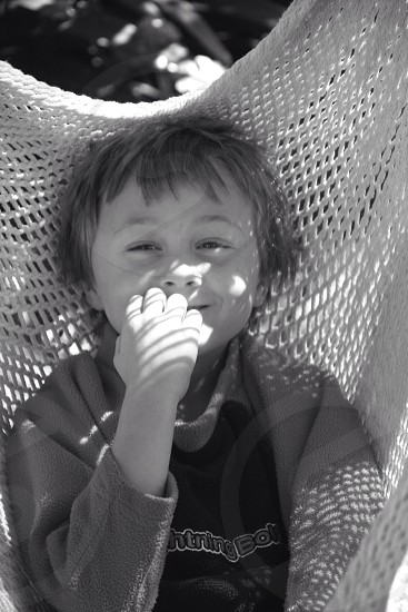 Black and white. Boy sitting in a hammock.  photo