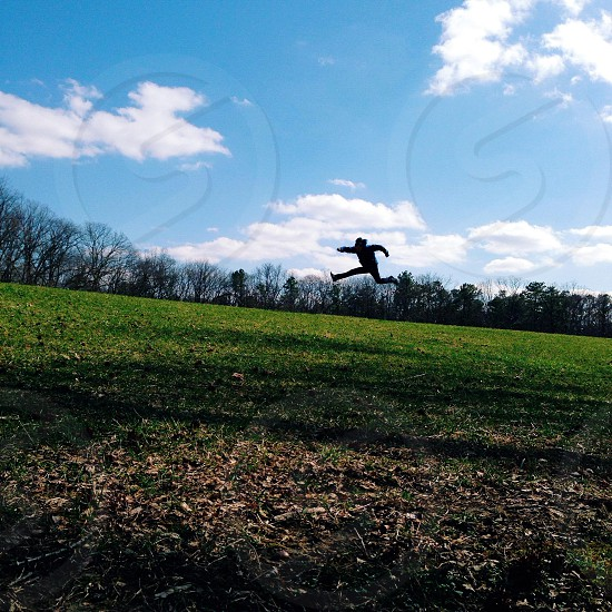 person jumping on green grass field photo