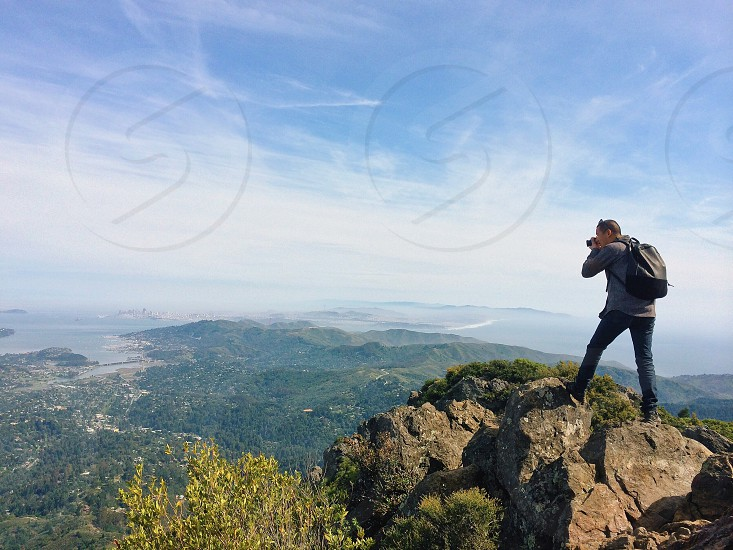 man wearing grey long sleeve shirt using camera on top of rock photo