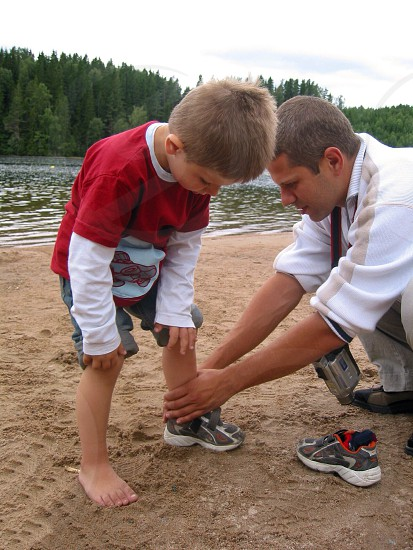 man in white collared shirt helping boy to wear shoes photo