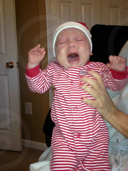 baby in striped red and white onesie with snaps crying photo