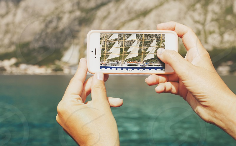 Phone camera capturing sailing boat entering the bay photo
