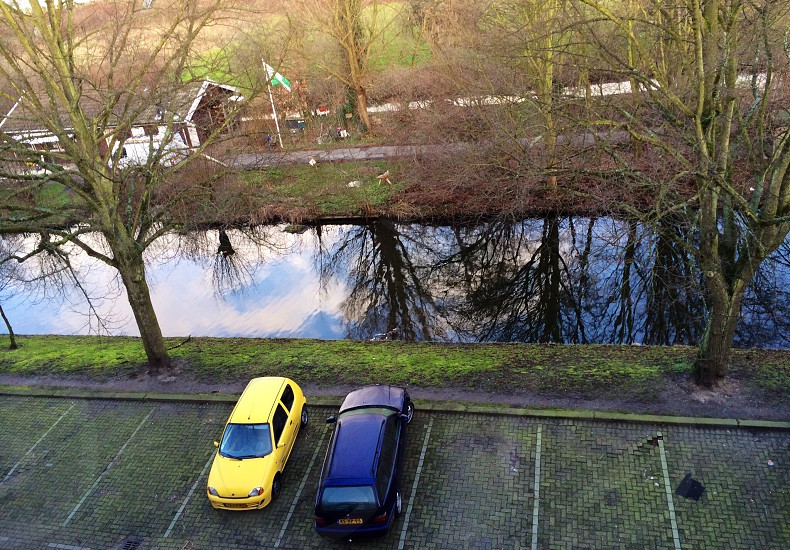 Cars parked on street with lots of space suggesting near nature and at the border of the cityline. Nice reflection of the sky in the water! photo