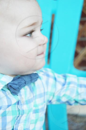 baby boy with blue eyest and redish brown eye brows side profile . He is wearing a blue bow tie and with a checkered blue and white shirt. He is sitting on a blue chair.  photo
