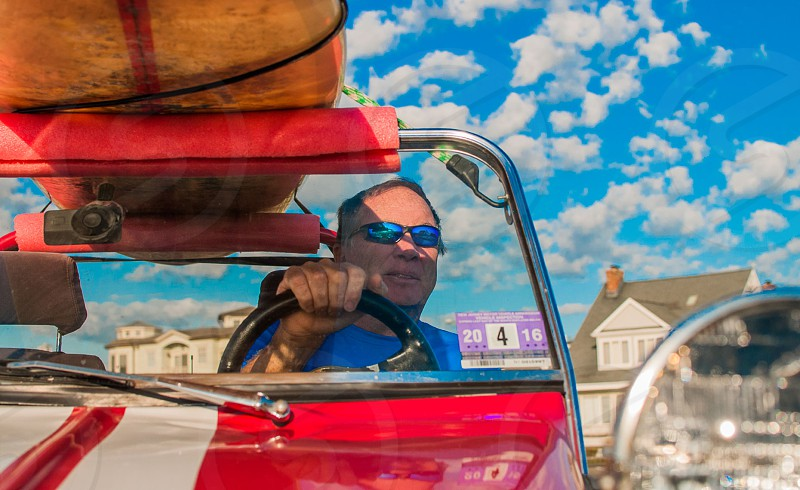 man in blue shirt and blue mirrored sunglasses driving a car photo