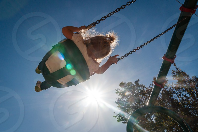 Little girl swinging high photo