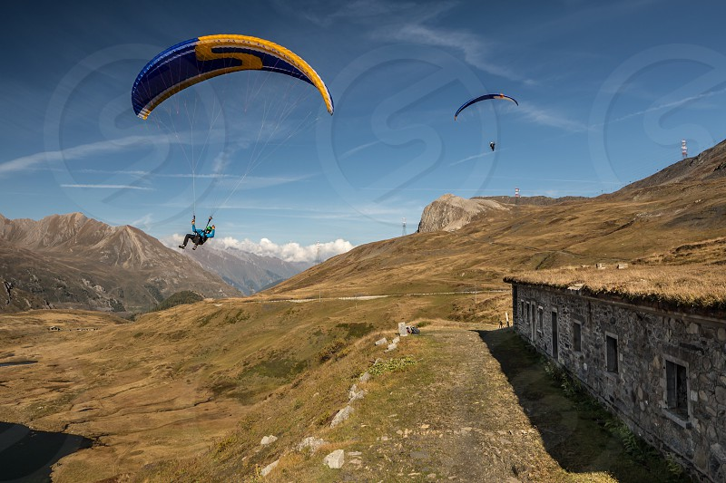 2 person paragliding above green grass field at daytime photo