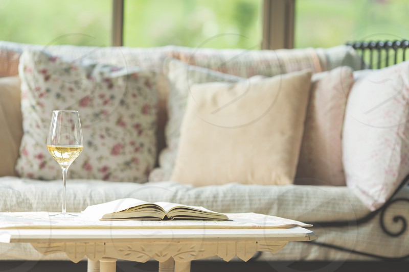 A wine glass sitting next to a book on in front of a daybed photo