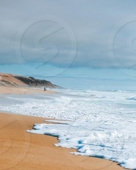 Ocean beach blue sand clouds calm  photo