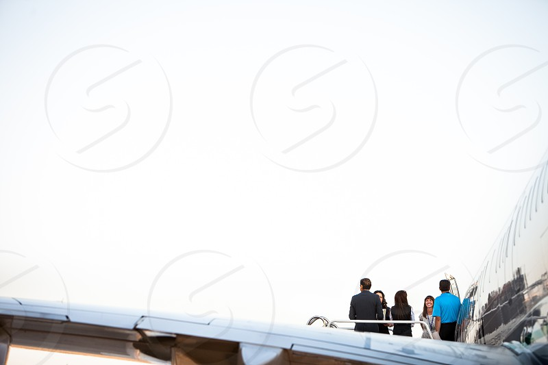 An excited crew waits at the top of the stairs leading to a commercial jet against a white sky. photo