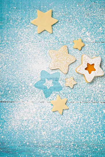 Christmas Linzer cookies with orange apricot jam and icing sugar on a blue background. photo