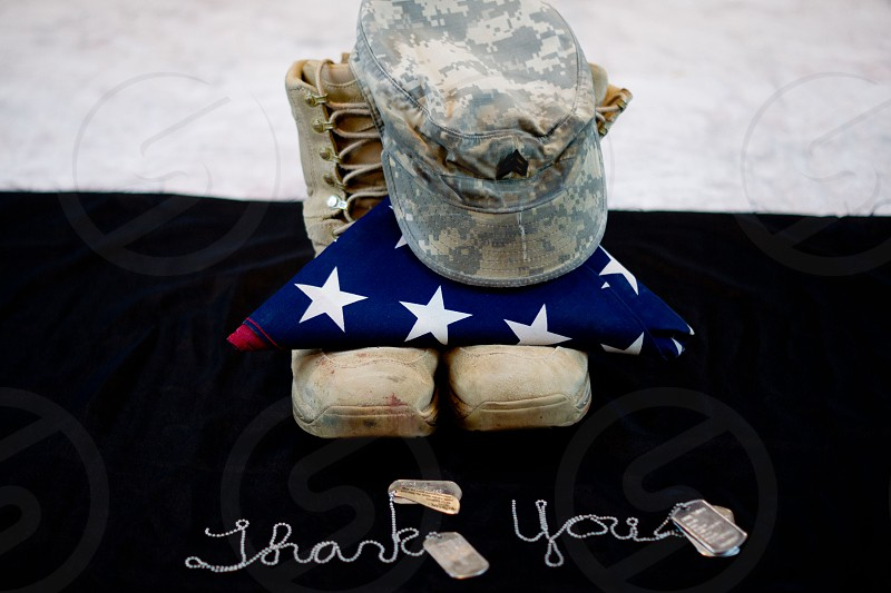 soldier's hat and combat boots resting with folded american flag photo