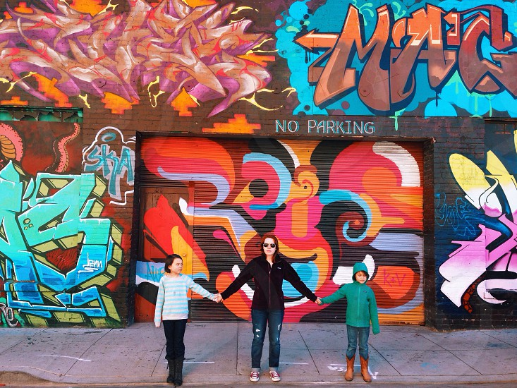 children and woman standing near building with graffiti photo