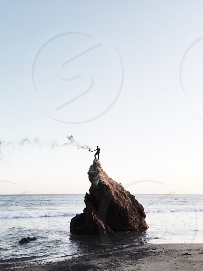 silhouette of man standing on top of rock in beach during daytime photo