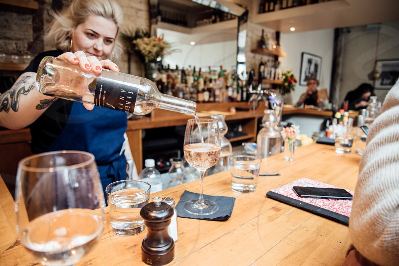 server pouring wine with brunch photo