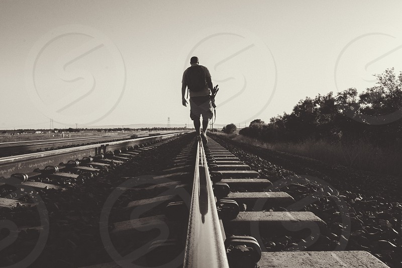 man walking along train tracks photo