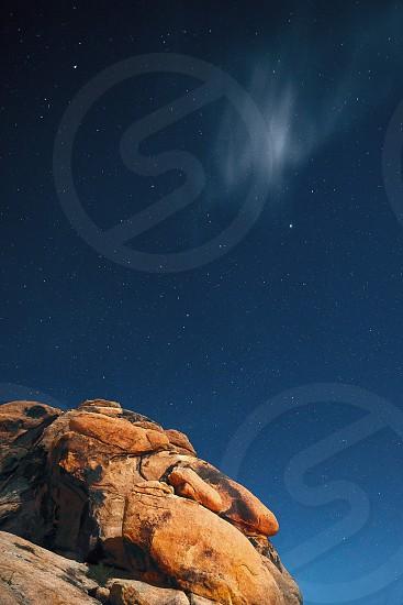 Stars in the night sky with red desert rock below. Location: Joshua Tree California photo