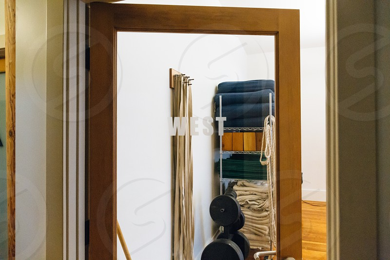 a brown wooden framed door made up of mirror reflecting the hanged straps dumbbells and folded textiles and wooden boxes placed on a rack photo