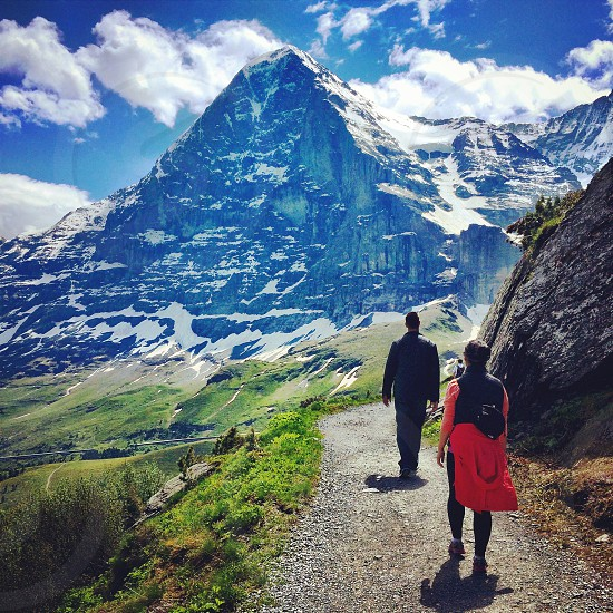 black icy mountain and people walking photo