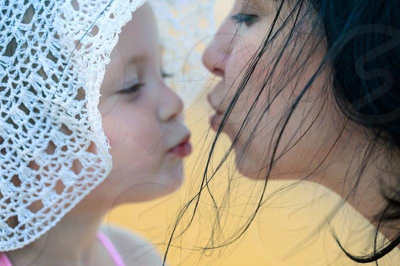 woman kissing girl wearing white crocheted sun hat photo