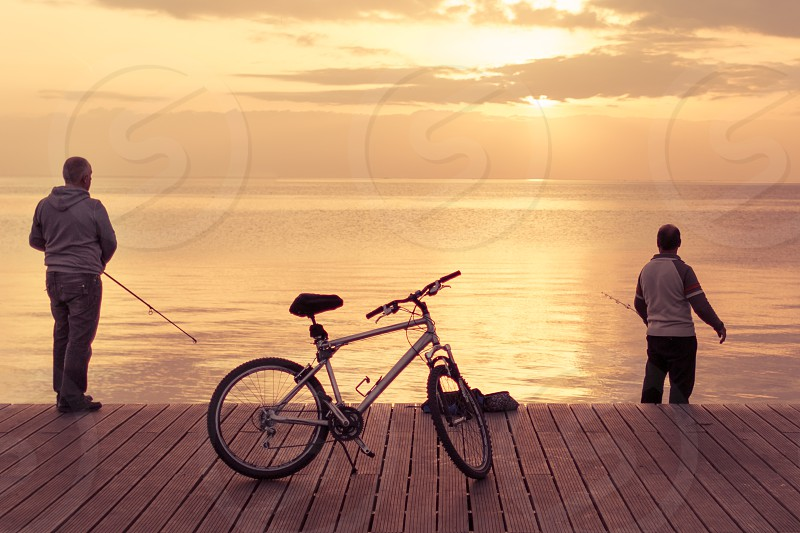 Fishermen And A Bicycle In The Sunset photo