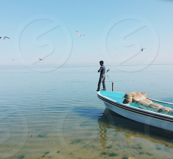 brunet man standing on prow of white canoe with blue lining photo