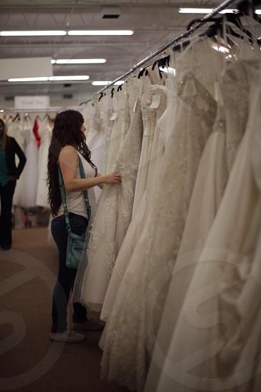 woman touching white wedding gown photo