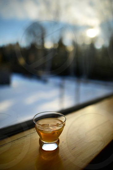 whiskey whiskey glass rye glass of rye winter scene window ledge on the rocks window view. photo