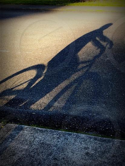 shadow boy riding bike street photo