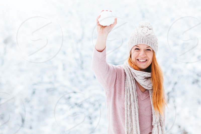 Young woman with snowball in the park photo