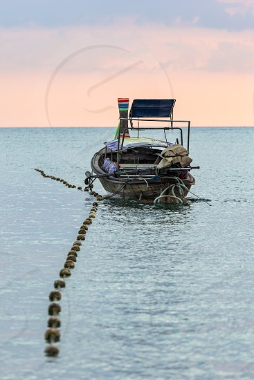 One moored longtail thai boat in calm sea water in the evening photo