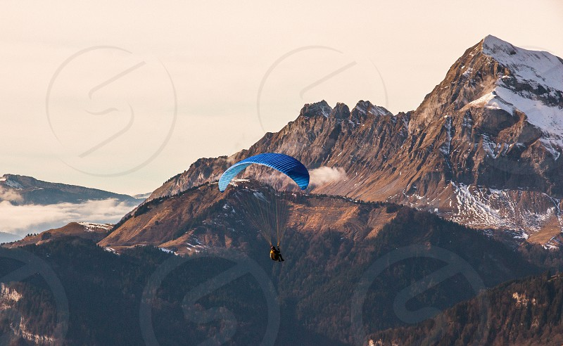 person riding on parachute above brown and white mountains during daytime photo