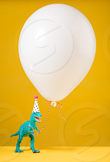 Teal dinosaur toy with birthday hat holding a white balloon on a yellow background. photo