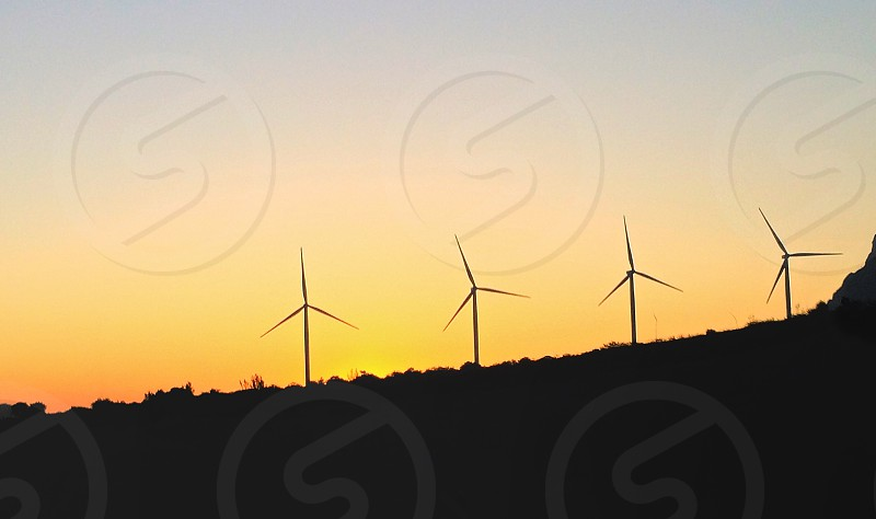 silhouette of 3 windmill on mountain at daytime photo