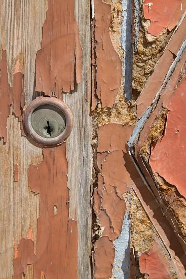 Rustic old wooden door with peeling orange paint and lock photo