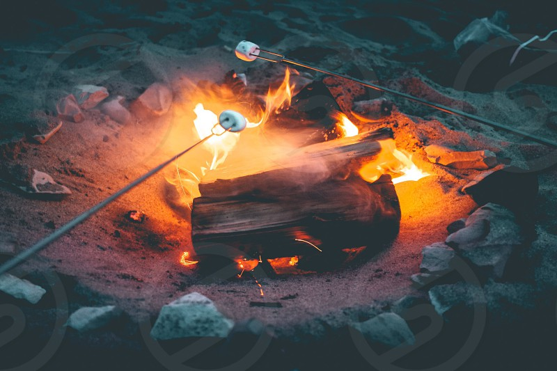 campfire beside gray rock near stainless steel fork with marshmallow photo